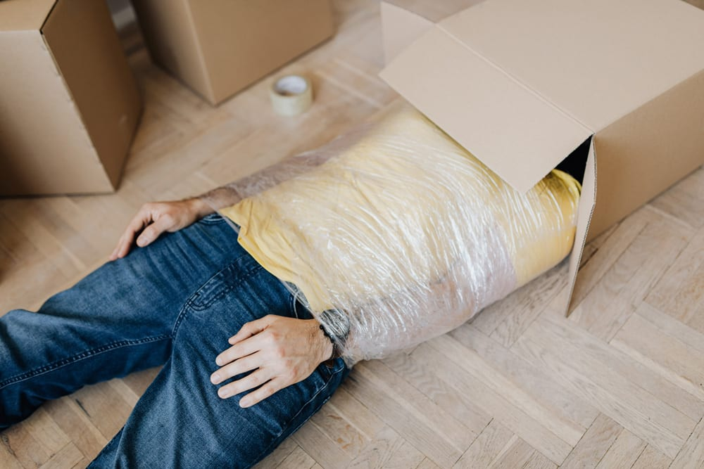 Man-tied-up-using-tape-with-head-in-carton-box