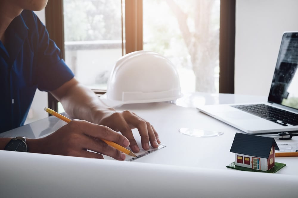 A property professional with a hard hat, laptop and model of a house; taking notes